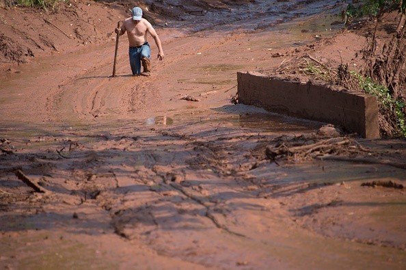 A man tries to cross a muddy area of Gesterio, part of the Barra Longo city, 60 km from Mariana, Brazil on November 07, 2015. Rescuers searched for a third day Saturday the site where an avalanche of mud and mining sludge buried a village in southeastern Brazil, as authorities struggled to pin down the number of dead and missing. AFP PHOTO / CHRISTOPHE SIMON (Photo credit should read CHRISTOPHE SIMON/AFP/Getty Images)
