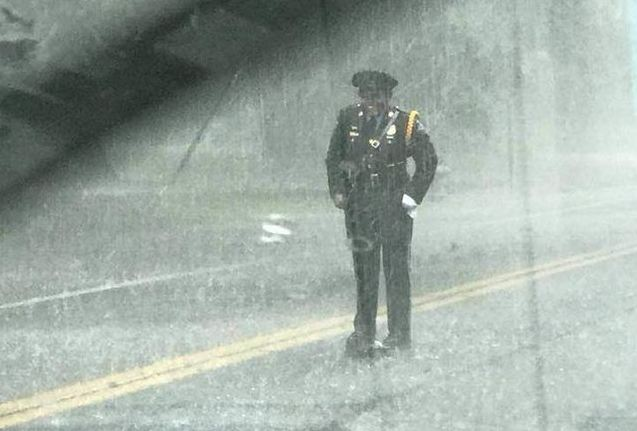 Cop Can't Help But Smile While Standing In The Rain Because She's Saving A Life